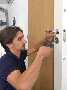 serrurier en train d'ouvrir une porte